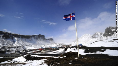 An Icelandic flag flies over Vik, a village sitting at the base of the Myrdalsjokull glacier, which is part of the ice cap sealing the Katla volcano, in Vik, on April 22, 2010. Katla, a volcano 10 times more powerful than neighbour Eyjafjallajökull, which erupted last week and impacted air traffic worldwide, has erupted in intervals of 40-80 years and its last eruption was in 1918. The village of Vik sits between the two main lava and glacial flood routes and has set up evacuation plans to abandon the village promptly if Katla erupts.