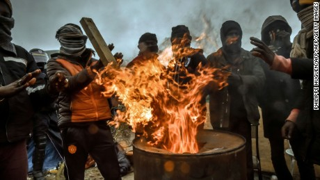 "Migrants keep warm as French authorities dismantle structures at the ""Jungle"" migrant camp in Calais Tuesday."