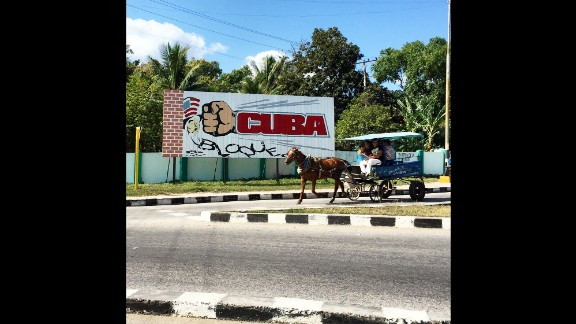 "CUBA: ""A horse drawn carriage in Cienfuegos travels past a billboard calling for an end to US sanctions on the island. Cuban government propaganda still paints the US as a hostile force but officials here have said they welcome President Obama's visit to the island next month. Almost every Cuban I know is excited for the long delayed thaw in relations that is happening before their very eyes."" - CNN's Patrick Oppmann @cubareporter."