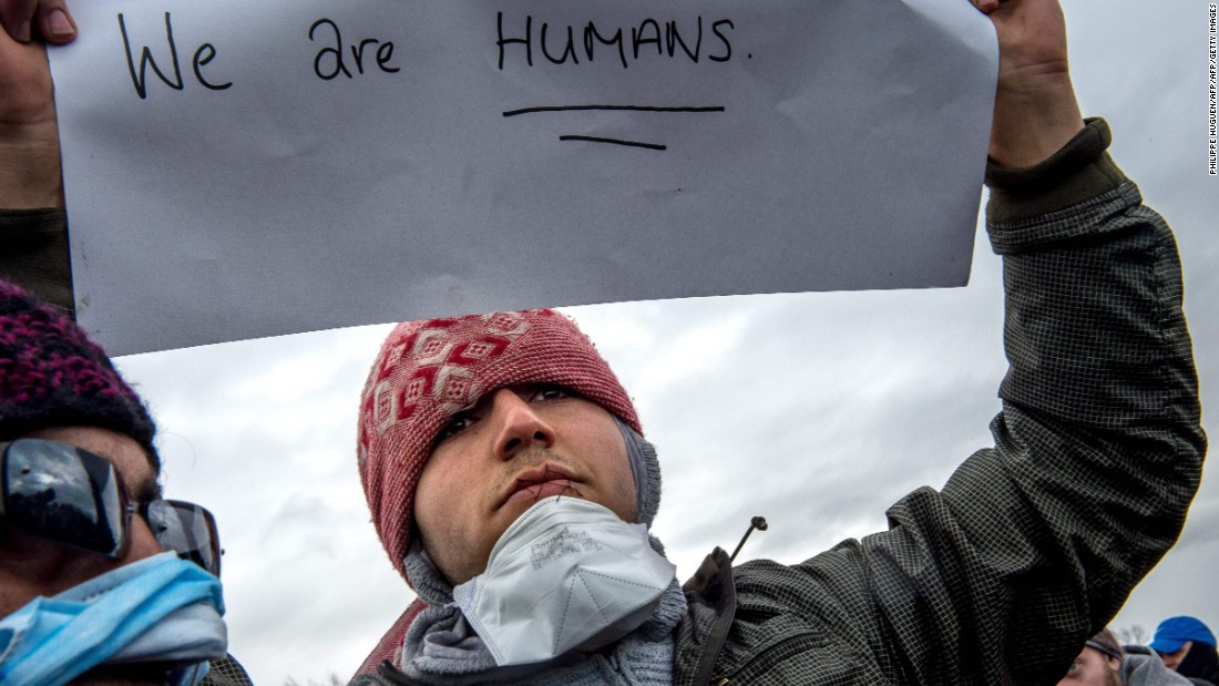"The migrants held signs saying ""We are humans"" and ""Where is your democracy?"" during a protest in the camp on Wednesday, March 2."