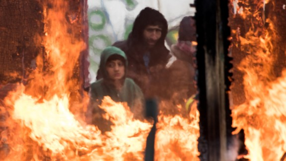 Migrants watch burning shacks in the southern part of the so-called