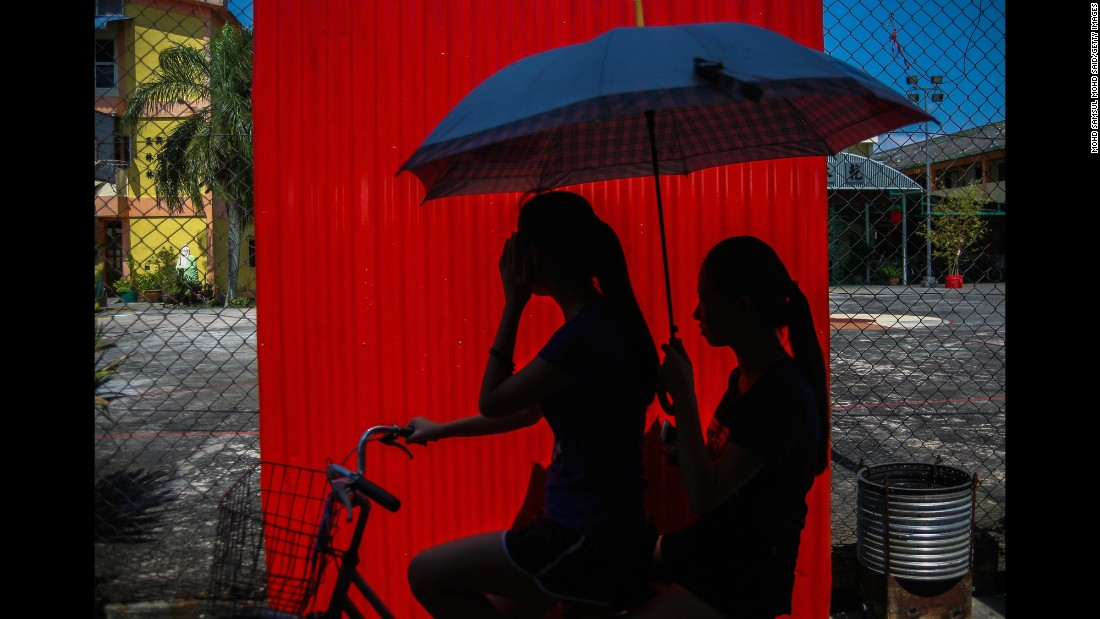 Women use an umbrella to block the sun as they ride a bike on Malaysia's Crab Island on Friday, February 26.