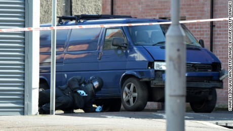 A bomb squad member inspects the prison officer's van on March 4 in east Belfast.