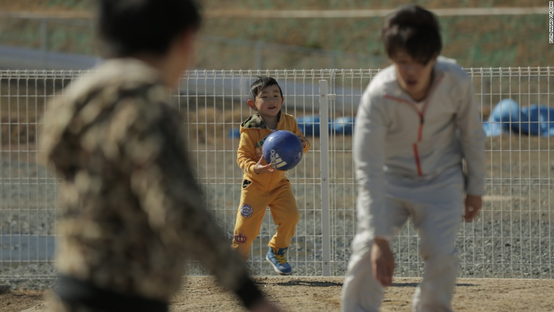 Children play in the dusty playground of a temporary housing complex in Japan's Fukushima prefecture.