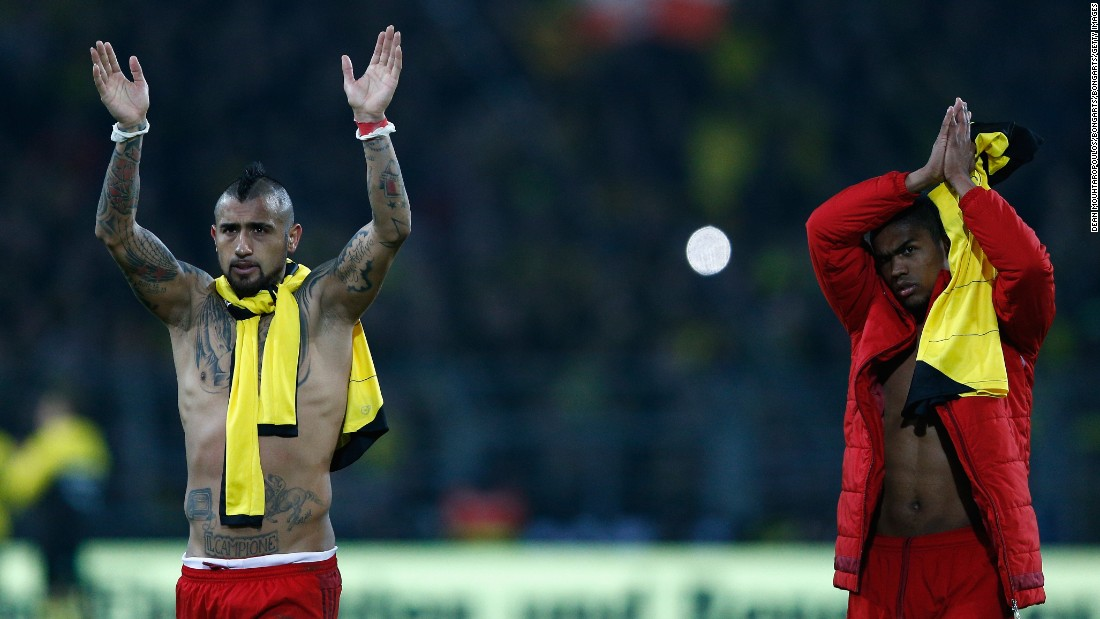 Arturo Vidal (L) and Douglas Costa salute fans at the final whistle. The result means Bayern remians five points clear atop the Bundesliga.