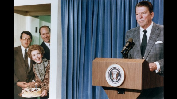President Reagan stands behind a lectern as first lady Nancy Reagan stands in a side doorway, planning to surprise him with a birthday cake on February 4, 1983, at the White House.