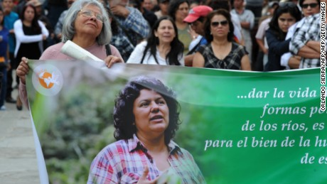 A mourner carries a banner honoring Caceres at her funeral.