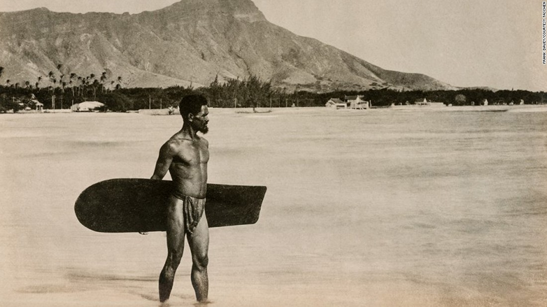 "This photo, taken in Honolulu around 1890, shows a man holding an alaia surfboard that was used for riding across gentle rolling waves. The image is just one of many vintage photos compiled by Jim Heimann for <a href=""https://www.taschen.com/pages/en/catalogue/popculture/all/01132/facts.surfing_17782015.htm"" target=""_blank"">Taschen's photo book ""Surfing.""</a>"