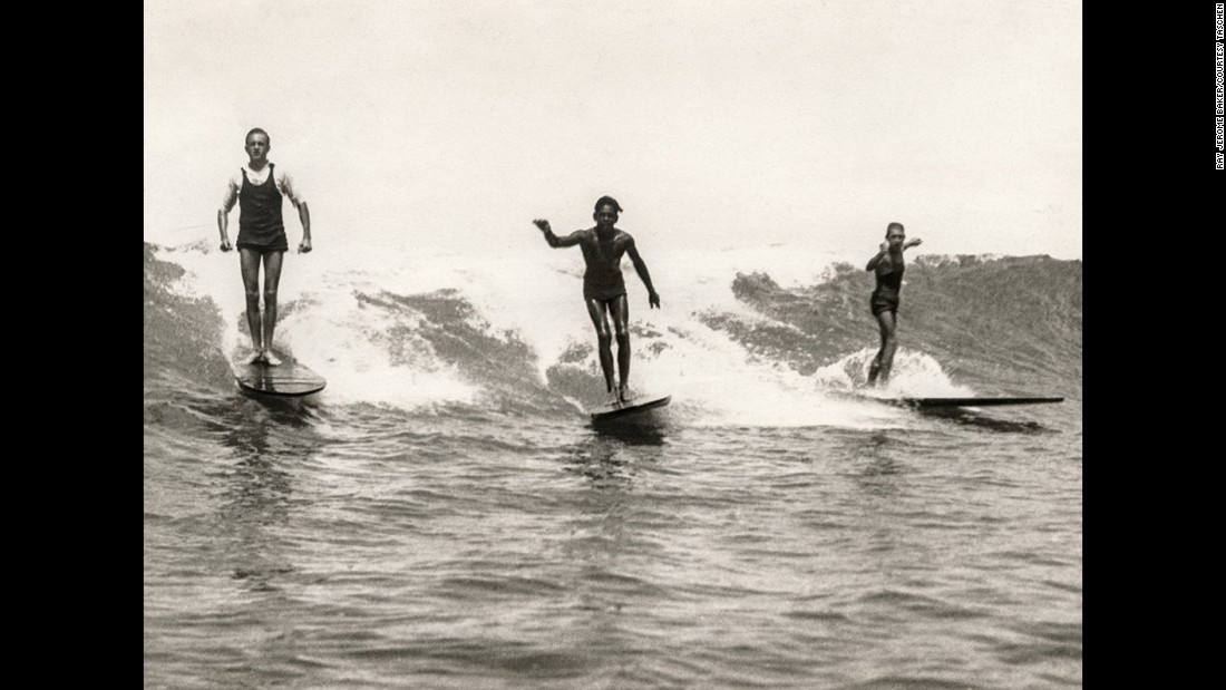 "George Freeth, left, surfs at Honolulu's Waikiki Beach around 1907. Freeth is often referred to as the ""father of modern surfing."" He insisted on riding upright rather than prone, angling across the wave rather than going straight in with the foam."