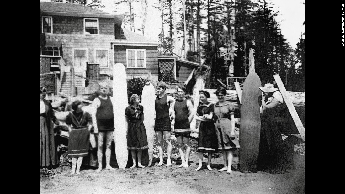 People with surfboards stand in front of a beach house in Joe Creek, Washington, around 1910. Surfing made its way to the Pacific Northwest via descendants of the Dole family of Hawaii, who built a sawmill and shingle factory near the Washington coast. They called it the Aloha Shake Company.