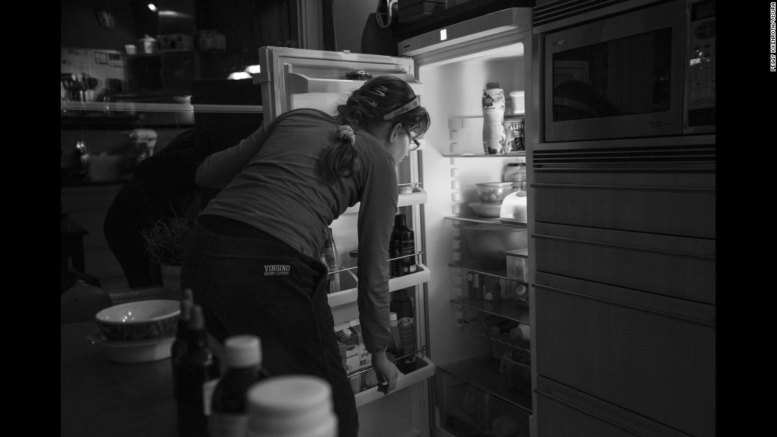 Suzanne looks in the fridge for a healthy snack that she's allowed to have in the afternoon. She has been on a limited diet since age 2.