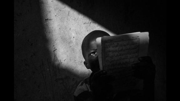 A talibé reads the Quran inside a school in Dakar.