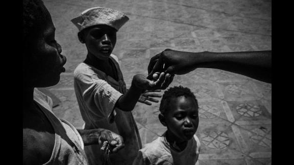A man gives money to talibés in Touba, Senegal.