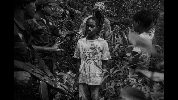 Military police approach a group of children walking through a forest area near the Guinea-Bissau border. Cruz learned that many talibés are kidnapped and trafficked from Guinea-Bissau.