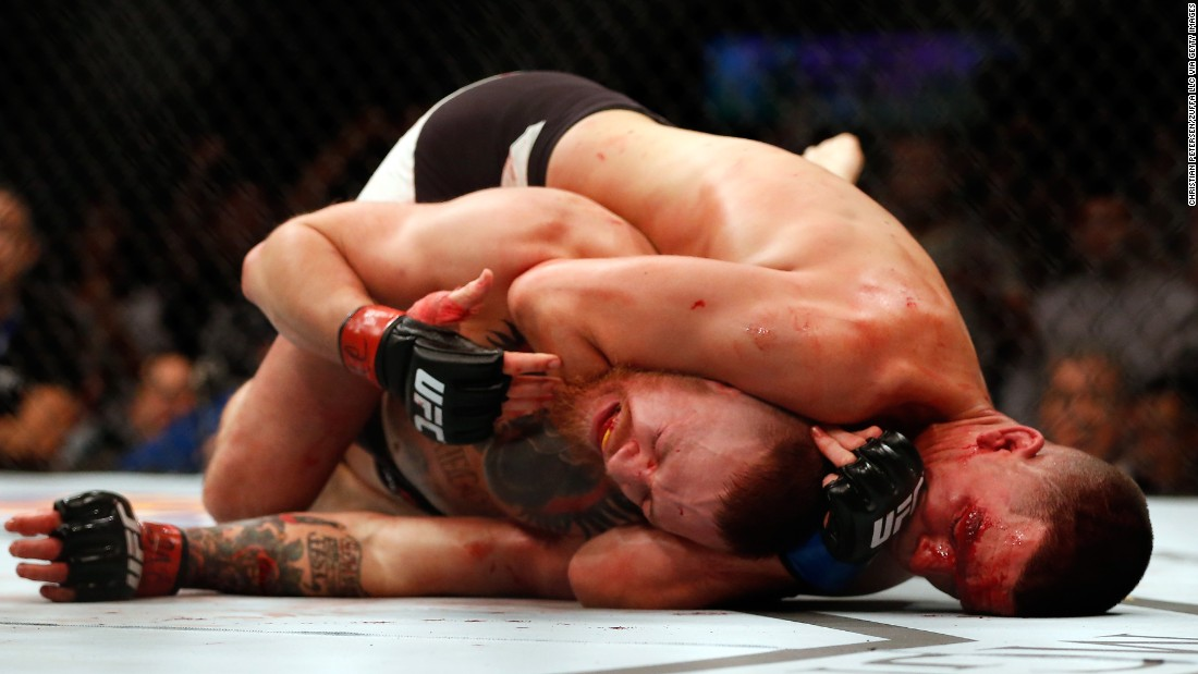 Nate Diaz chokes Conor McGregor on his way to winning the main event of UFC 196 on Saturday, March 5. The second-round submission was McGregor's first loss since November 2010.