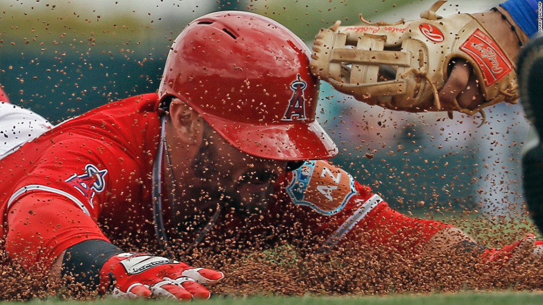 Johnny Giavotella, a second baseman with the Los Angeles Angels, slides safely into third after hitting a triple in Tempe, Arizona, on Sunday, March 6.