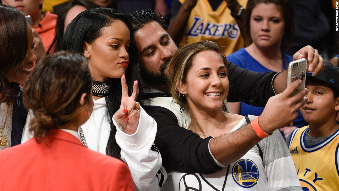 Singer Rihanna flashes the peace sign as she poses with a fan at an NBA game in Los Angeles on Sunday, March 6.