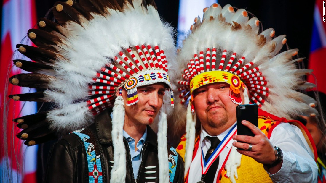 Canadian Prime Minister Justin Trudeau, left, poses with an elder of the Tsuut'ina First Nation after receiving a ceremonial headdress Friday, March 4, near Calgary, Alberta.
