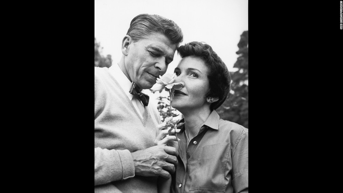 The Reagans smell a flower at their home in 1955.
