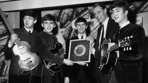 "Sir George Martin, the music producer whose collaboration with the Beatles helped redraw the boundaries of popular music, died March 8, according to his management company. He was 90. Above, Martin poses with the Beatles after the album ""Please Please Me"" went silver in 1963."