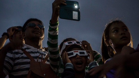 Special filters are needed in order to view the sun safely. Here, a crowd in Palembang city in Indonesia
