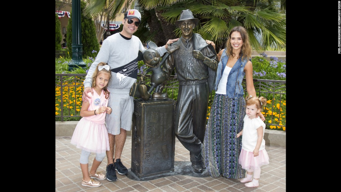 Jessica Alba and husband Cash Warren pose with daughters Haven and Honor Warren with a bronze statue of a young Walt Disney and Mickey Mouse. Alba hired a Spanish professor to teach her and Honor to speak Spanish.
