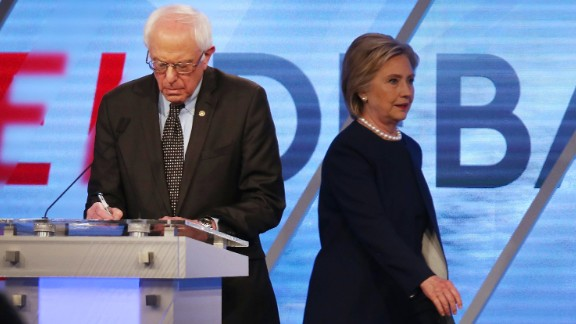Democratic presidential candidate Senator Bernie Sanders (D-VT) and Democratic presidential candidate Hillary Clinton are seen on stage during a break in the broadcast of the Univision News and Washington Post Democratic Presidential Primary Debate at the Miami Dade College
