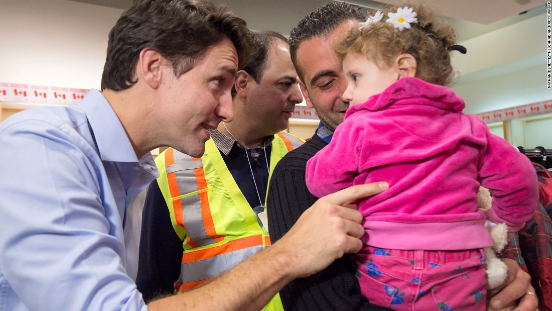 Trudeau greets Syrian refugees Kevork Jamkossian and daughter Madeleine during their arrival at Toronto's Pearson International Airport in December 2015. The new Prime Minister pledged to take in and resettle 25,000 Syrian refugees in Canada.