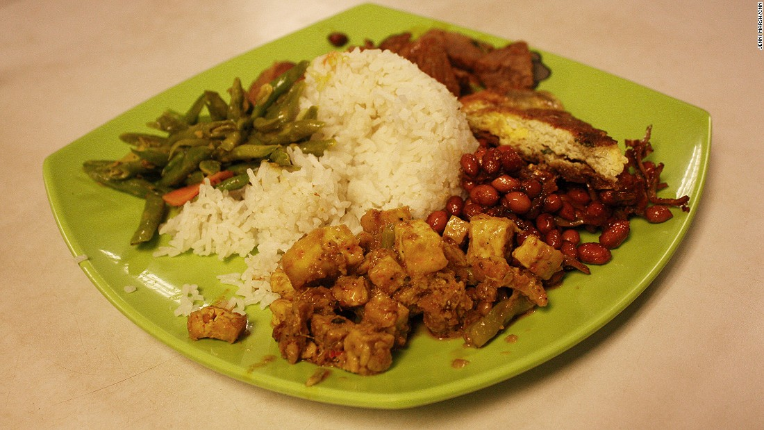 Nasi padang, a Malay dish, here is comprised of steamed rice, vegetables,   peanuts, anchovies, tofu, beef, and potato patties.
