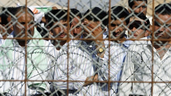 Detainees stand in the Abu Ghraib prison yard while waiting to be released on June 27, 2006, in Baghdad, Iraq.