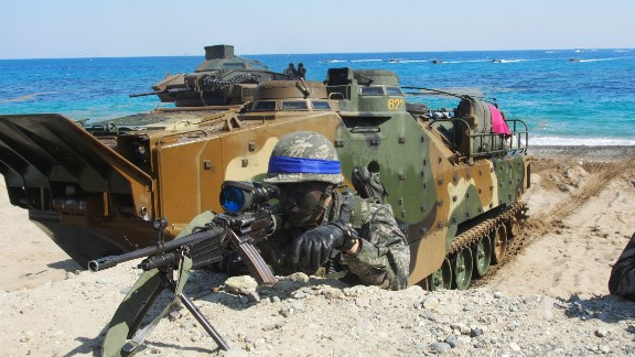 A South Korean Marine looks through his rifle's view finder on March 12 with an amphibious assault vehicle in the background.