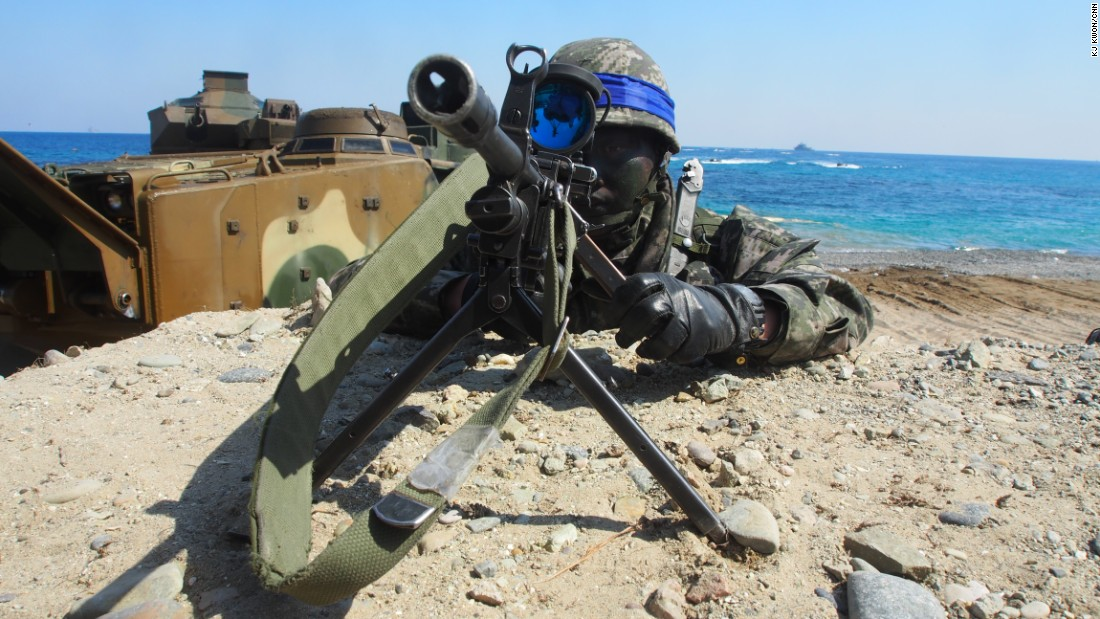 A South Korean Marine looks through a viewfinder on a sniper rifle on March 12. Marines and sailors stormed a beach aboard assault vehicles in a mock amphibious assault.