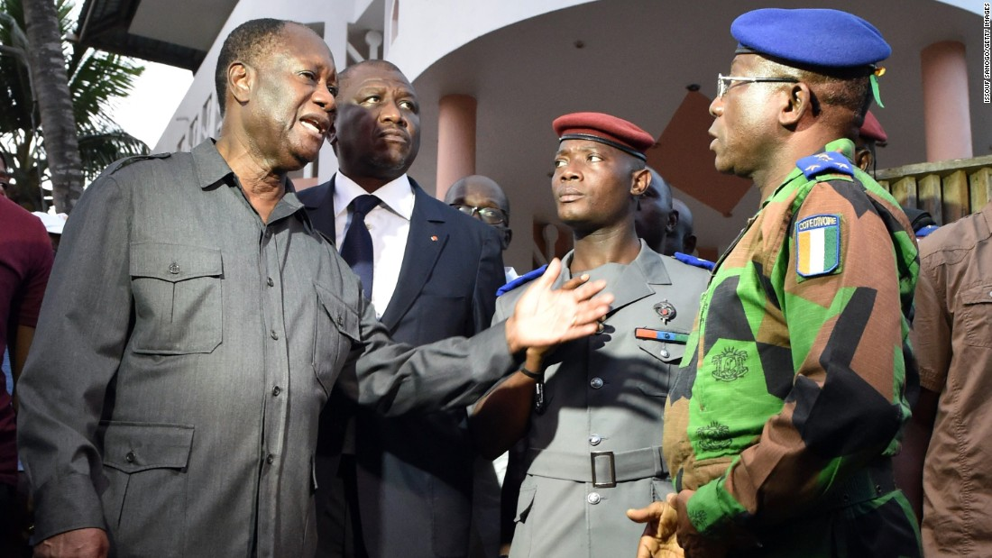 Ivory Coast President Alassane Ouattara, left, speaks to the country's chief of staff, Gen. Soumaila Bakayoko.