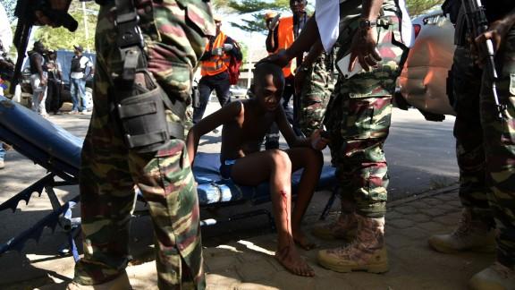 Ivorian soldiers stand around a boy who was injured.