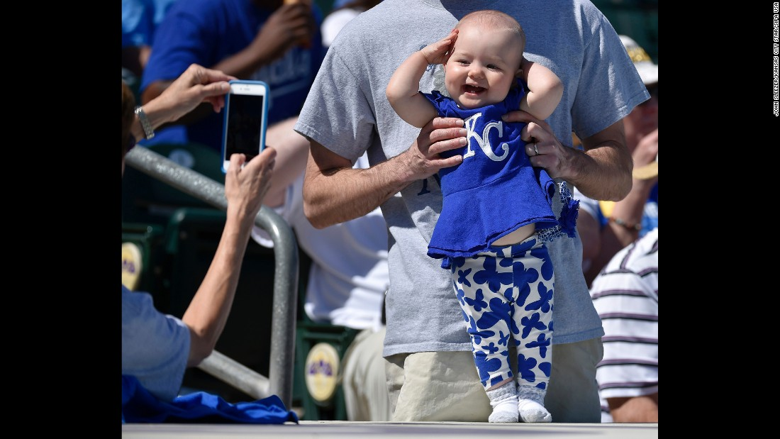 A happy 10-month old Kansas City Royals fan, Sydney Barth, from South Carolina, poses for a photograph on top of the dugout before a spring training game against the Colorado Rockies on Tuesday, March 8, in Surprise, Arizona.