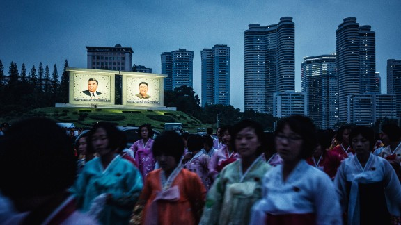 Women in traditional Korean dress head to the dance. Though much of North Korea is without electricity, the portraits of the supreme leaders are illuminated brightly.