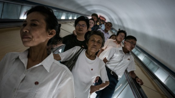 North Koreans head down to the Pyongyang Metro. It's 100 meters underground thus riding the escalator down to the station takes a couple of minutes.