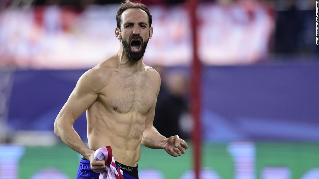 Veteran Atletico Madrid defender Juanfran rips his shirt off in celebration after scoring the decisive penalty in the shootout to knock out PSV.