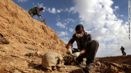 An Iraqi man inspects on February 3, 2015, the remains of members of the Yazidi minority killed by the Islamic State (IS) jihadist group after Kurdish forces discovered a mass grave near the village of Sinuni, in the northwestern Sinjar area.