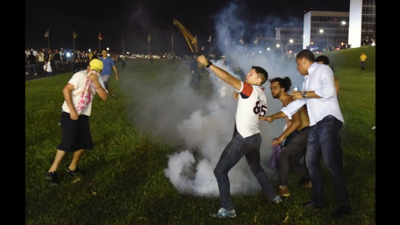 Demonstrators throw tear gas back at riot police during a protest in Brasilia on March 16.