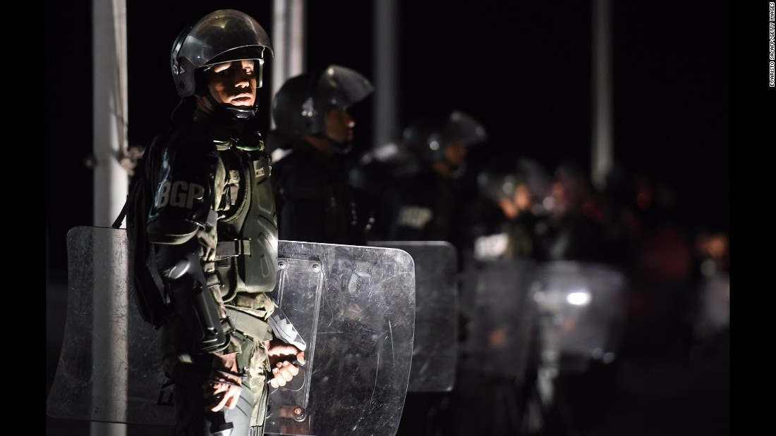 Riot police stand guard outside the presidential palace in Brasilia on March 16.