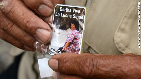 "A man holds a card bearing a picture of murdered indigenous activist Berta Caceres reading ""Bertha lives. The fight continues"" during her funeral in La Esperanza, 200 km northwest of Tegucigalpa, on March 5, 2016. Honduran indigenous activist Berta Caceres, a renowned environmentalist whose family has labeled her killing an assassination, was shot dead on March 3 at her home in La Esperanza. Caceres rose to prominence for leading the indigenous Lenca people in a struggle against a hydroelectric dam project that would have flooded large areas of native lands and cut off water supplies to hundreds.  AFP PHOTO / ORLANDO SIERRA / AFP / ORLANDO SIERRA        (Photo credit should read ORLANDO SIERRA/AFP/Getty Images)"