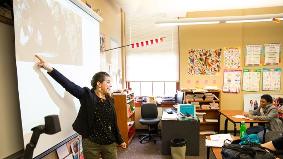 """Gretchen Sloan, Marcelas' Spanish teacher, shows her class the famous photo of Marcelas as the """"Obamacare kid"""" six years ago. Marcelas says most of her classmates are too young to remember all the fuss over Obamacare and weren't impressed with her involvement in one of the nation's most divisive political issues."""