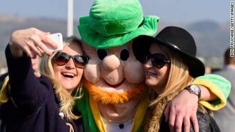 CHELTENHAM, ENGLAND - MARCH 17:  A man wearing a leprechaun fancy dress suit poses for a selfie during St Patrick's Day at the Cheltenham Festival at Cheltenham Racecourse on March 17, 2016 in Cheltenham, England. The four day annual jump racing event sees jockeys compete for a piece of the 4.1 million GBP of the prize money.  (Photo by Ben Pruchnie/Getty Images)