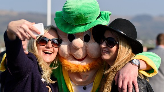 A man wearing a leprechaun fancy dress suit poses for a selfie during St Patrick's Day at the Cheltenham Festival at Cheltenham Racecourse on March 17, 2016