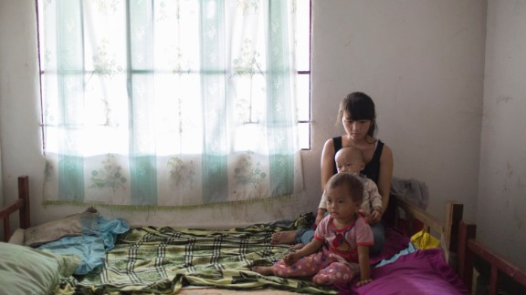 Mei, 16, sits on bed with her 2-year-old daughter and 1-year-old son in Wanhe village, Mengla county, Yunnan province. She has been married for 2 years. She and her husband were classmates in primary school and they dropped out from school after getting married.