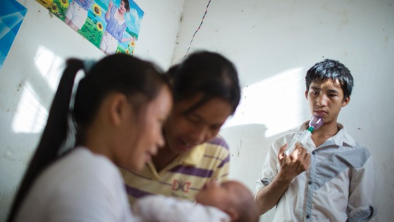 Ming holds a breast pump as he watches his wife, Cai, and his mother care for his newborn son.