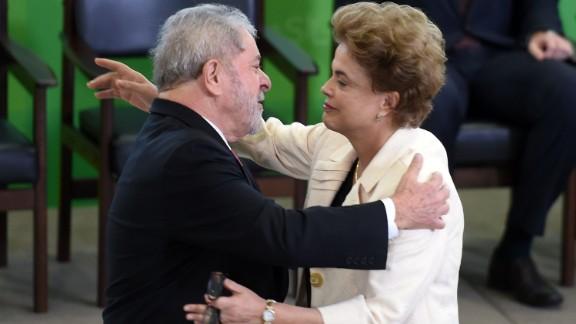 Former Brazilian president Luiz Inacio Lula da Silva (L) hugs Brazilian president Dilma Rousseff during Lula