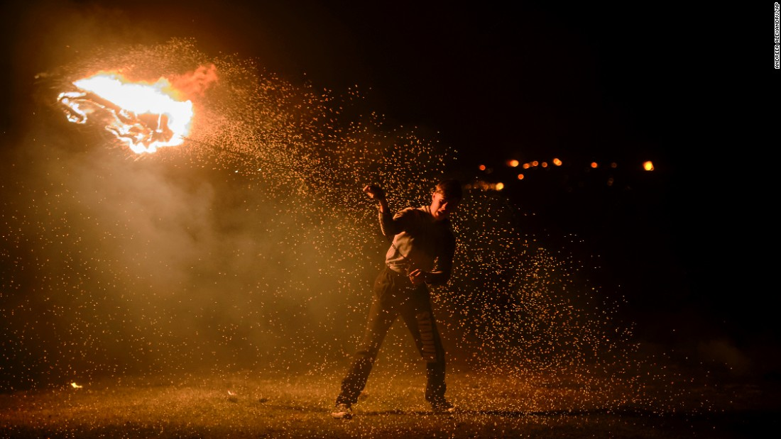 A young man spins a flaming car tire on a metal chain Sunday, March 13, during a celebration in Romania marking the first day of Great Lent.