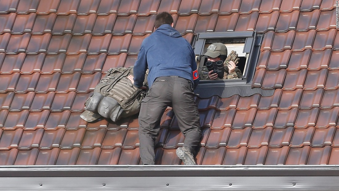 "Police officers take positions on top of a roof during a police operation in Brussels, Belgium, on Tuesday, March 15. One suspect died and four police officers were wounded in <a href=""http://www.cnn.com/2016/03/15/europe/brussels-paris-attacks-shots-fired/"" target=""_blank"">a raid linked to the Paris terror attacks.</a>"